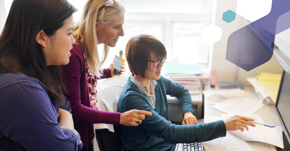 faculty member and student pharmacists reviewing data on computer screen